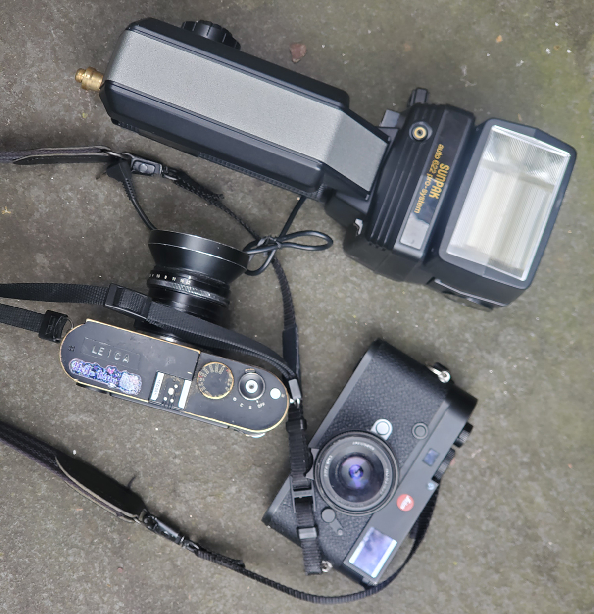 two small cameras and a large flash lying on the ground
